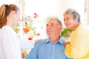 Happy elderly couple talking with their carer